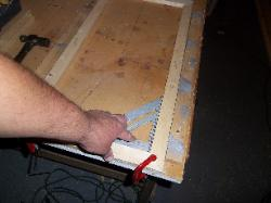 Canvas frame being squared in holding jig